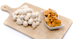 White button and chanterelle mushrooms on a wooden board